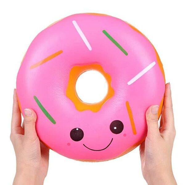 squishy géant donut rose dans les mains